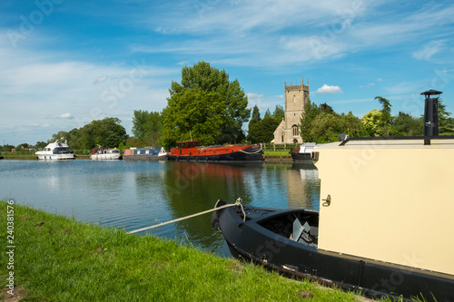 Spring sunshine on boats moored by St Marys Church on the Gloucester & Sharpness Canvas Print