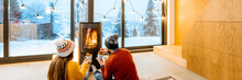 Young Couple Dressed In Bright Sweaters Sitting Near The Fireplace In The Modern House In The Mountains Durnig Winter Time