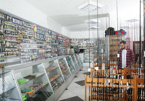 Customer choosing fishing equipment in sports shop