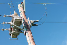 A Close Up Of A British Electric Pole Transformer Taken Against A Bright Blue Sky