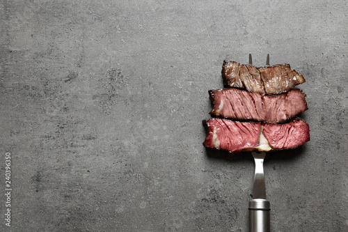 Fotobehang Steakhouse Fork with pieces of delicious barbecued meat on gray background, top view. Space for text