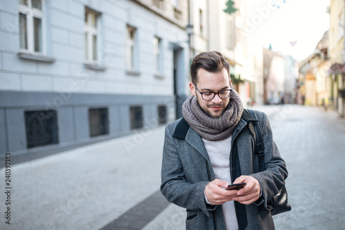 Foto  Young entrepreneur walking in the city, using smartphone.