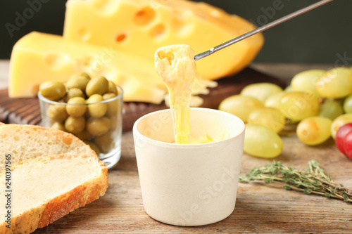 Piece of bread over bowl with delicious cheese fondue on wooden table