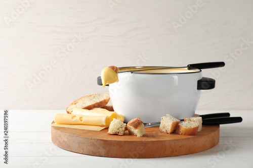Pot of delicious cheese fondue and fork with bread on wooden table