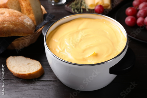 Pot with delicious cheese fondue on wooden table