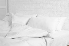 Large Comfortable Bed With Pillows And Blanket Near White Brick Wall Indoors. Stylish Interior