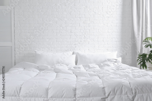 Large comfortable bed with pillows and blanket near white brick wall indoors Canvas Print