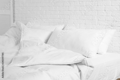 Fotomural Large comfortable bed with pillows and blanket near white brick wall indoors