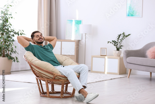 Fotografie, Obraz  Handsome young man sitting in armchair at home. Space for text
