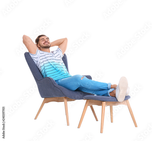 Fotografie, Obraz  Handsome young man relaxing in armchair with legs on footrest against white back