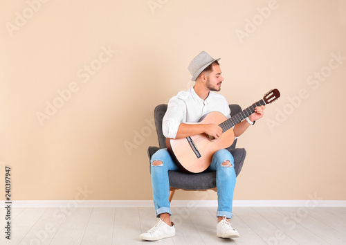 Handsome young man with guitar in armchair near color wall indoors Fototapet