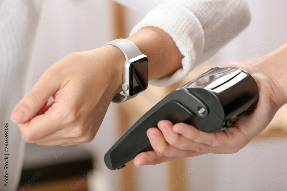 Fototapeta Woman using terminal for contactless payment with smart watch indoors