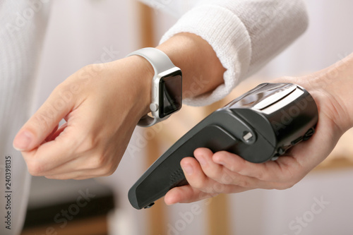 Photo Woman using terminal for contactless payment with smart watch indoors
