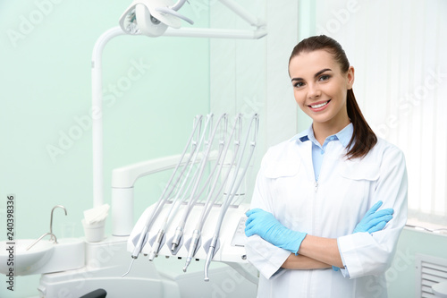 Młody żeński dentysta w białym żakiecie przy miejscem pracy. Miejsce na tekst