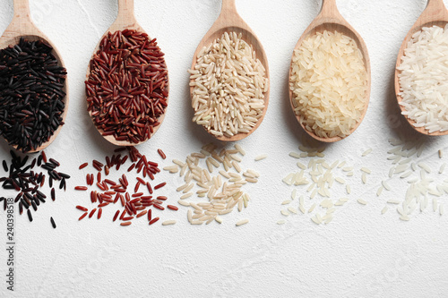 Photo Stands Herbs 2 Flat lay composition with brown and other types of rice in spoons on white background