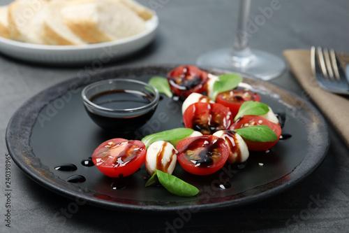 Fresh vegetable salad with mozzarella and balsamic vinegar on plate, closeup