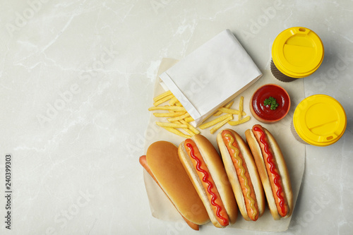 Tasty hot dogs, french fries and drinks on table, top view. Space for text