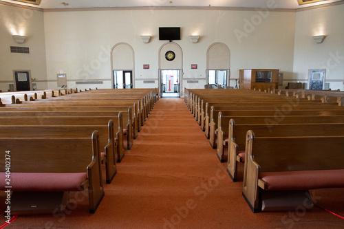 Fototapeta wide angle shot of interior of empty church lit by faint sunlight obraz