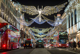 Fototapeta Londyn - Red double-decker buses pass under twinkling Christmas lights along the upscale shopping district of Regent Street.