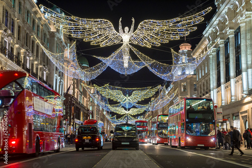 Fotografie, Tablou  Red double-decker buses pass under twinkling Christmas lights along the upscale shopping district of Regent Street
