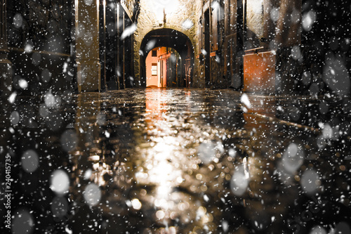 Photo Stands Narrow alley Kilkenny Ireland historic Butterslip alley with snowflakes falling during winter snow storm