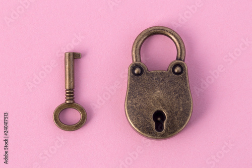 bronze key and padlock on gently pink paper, background image Tableau sur Toile