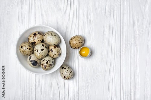Top view on small quail eggs on white wooden background