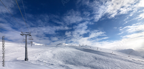 Ski slope, chair-lift on ski resort and blue sky with sunlight clouds