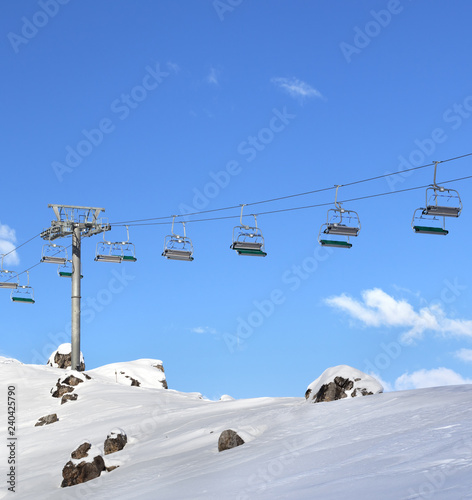 Sunlight chair-lift and blue sky with clouds at ski resort on sunny day