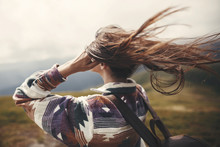 Stylish Hipster Girl With Backpack  And Windy Hair On Top Of Mountains. Portrait Of Happy Young Woman Relaxing. Carefree Mood. Amazing Atmospheric Moment