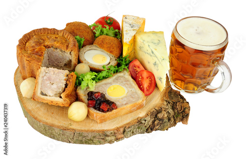 Traditional ploughman's buffet lunch ingredients with a pint of beer isolated on a white background