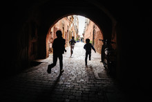 Silhouette Of Boys Running Through A Tunnel In Marrakech, Morocco