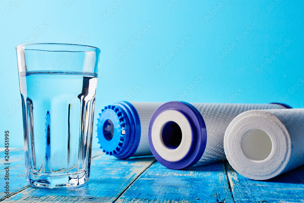 Fototapeta Water filters. Carbon cartridges and a glass on a blue background. Household filtration system.