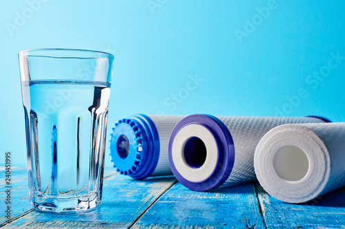 Obraz Water filters. Carbon cartridges and a glass on a blue background. Household filtration system. - fototapety do salonu