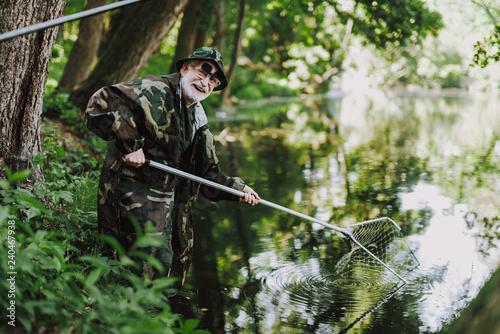 Fotografia  Joyful aged angler enjoying his fishing weekend