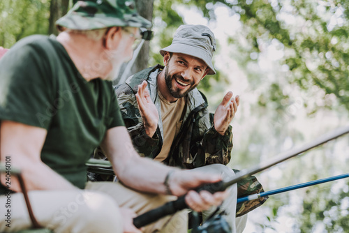 Foto  Emotional bearded man fishing with his elderly father