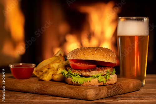 Hamburger with potato and beer on the fireplace background.