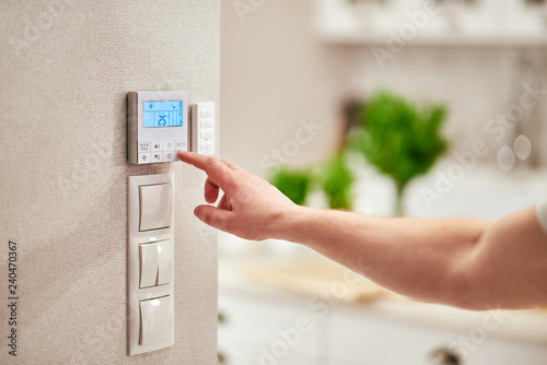 Photo Male hand adjusting temperature / thermostat