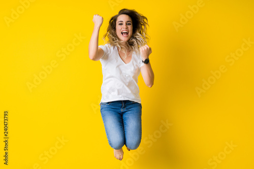 Fotografie, Tablou  Beautiful young blonde woman jumping happy and celebrating with raised hands and
