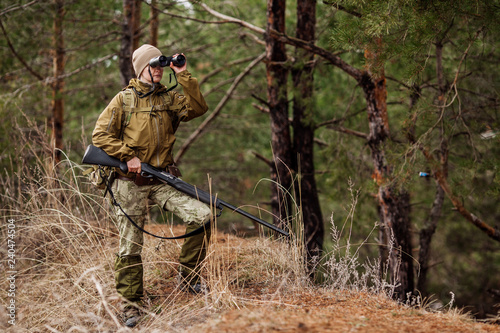 Fotografie, Obraz Female hunter in camouflage clothes ready to hunt, holding gun and walking in forest