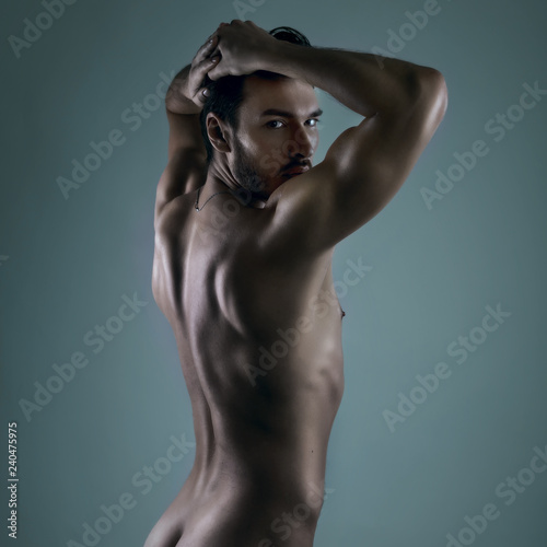 Naked athletic handsome man back. Fashion portrait of nude young man standing side-back and holds hands on the head. Expressive look face on dark grey background