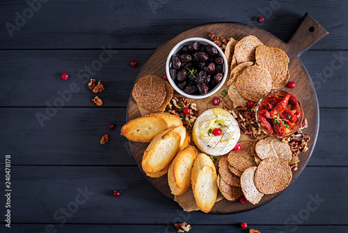Traditional french baked camembert cheese with thyme and toast, walnuts, olives, sun dried tomatoes, and flax chips. Top view.