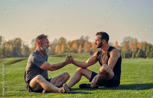 The old and young sportsmen handshaking on the grass Canvas Print