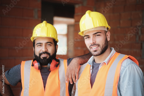 Obraz Happy Construction Workers Smiling At Camera In New Building - fototapety do salonu