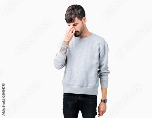 Fotografia  Young handsome man wearing sweatshirt over isolated background tired rubbing nose and eyes feeling fatigue and headache