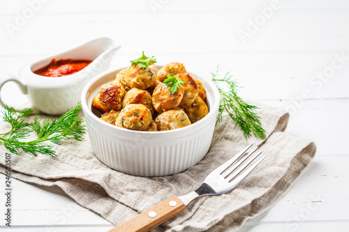Fotografie, Obraz  Healthy chicken meatballs with greens and tomato sauce on white background