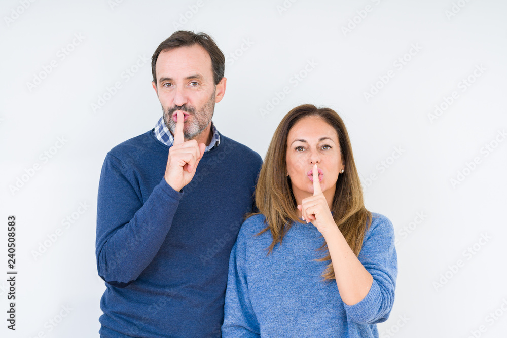 Fototapeta Beautiful middle age couple in love over isolated background asking to be quiet with finger on lips. Silence and secret concept.