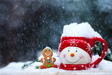 Close-up Of Cup With Snowman Face And Gingerbread At Snowfall