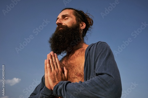 Fotografía  handsome bearded male with namaste hands in blue clear sky background