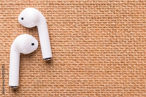Fotografía  White wireless headphones on a beautiful wicker napkin